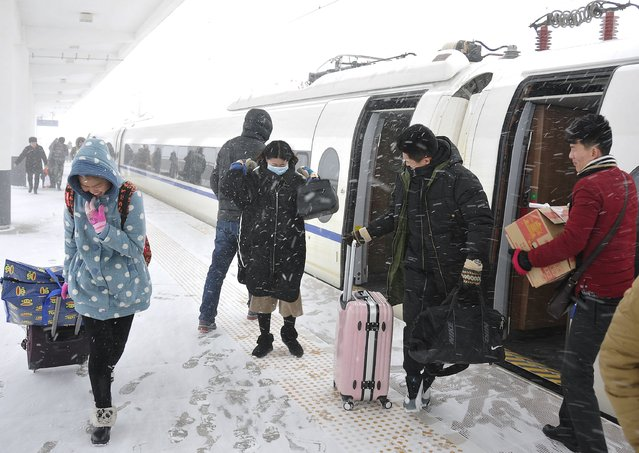 Passengers walk against snow as they get off a train at a railway station in Qingrong, Shandong province, China, January 24, 2016. (Photo by Reuters/China Daily)