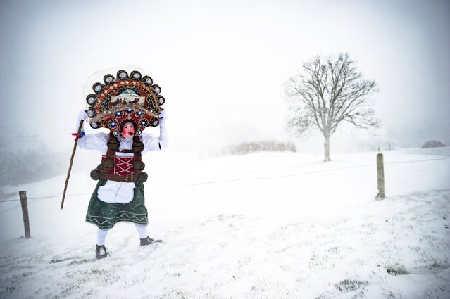 A so-called Silvesterchlaus (New Year Clause) holds on to his hat during heavy winds on his way in Waldstatt, Switzerland, January 13, 2016, to offer his best wishes for the New Year (following the Julian calendar) to the farmers in this region. (Photo by Gian Ehrenzeller/EPA )
