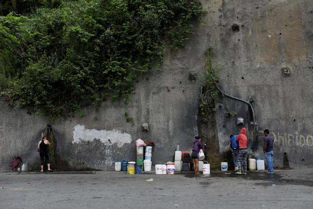 People fill containers with water coming from a mountain, in a road at Plan de Manzano slum in Caracas, July 20, 2018. Around 11 percent said they thought dirty water had caused skin and stomach problems. The survey does not have comparative figures. Medical consequences are hard to gauge as the Health Ministry no longer releases once-weekly data, but doctors say scabies and diarrhea are on the rise. (Photo by Marco Bello/Reuters)
