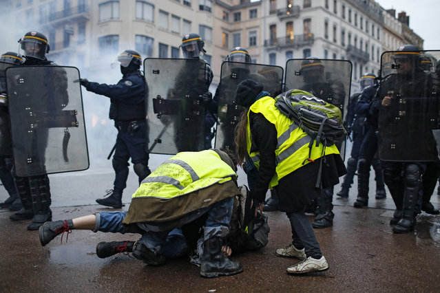 Police officers clash with demonstrators in Lyon, central France, Saturday, December 8, 2018. The grassroots movement began as resistance against a rise in taxes for diesel and gasoline, but quickly expanded to encompass frustration at stagnant incomes and the growing cost of living. (Photo by Laurent Cipriani/AP Photo)