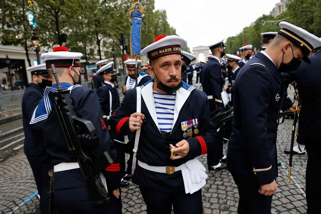 """A member of the French Navy from the """"Ecole des Mousses"""" get ready as preparations are made for the annual Bastille Day military parade on the Champs-Elysees avenue in Paris on July 14, 2021. (Photo by Ludovic Marin/AFP Photo)"""
