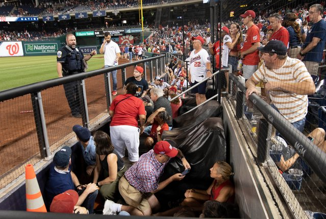 Fans rush to evacuate after hearing gunfire, during a baseball game between the San Diego Padres and the Washington Nationals at Nationals Park in Washington on Saturday July 17, 2021. The game was suspended in the sixth inning after police said there was a shooting outside the stadium. (Photo by John McDonnell/The Washington Post via AP Photo)