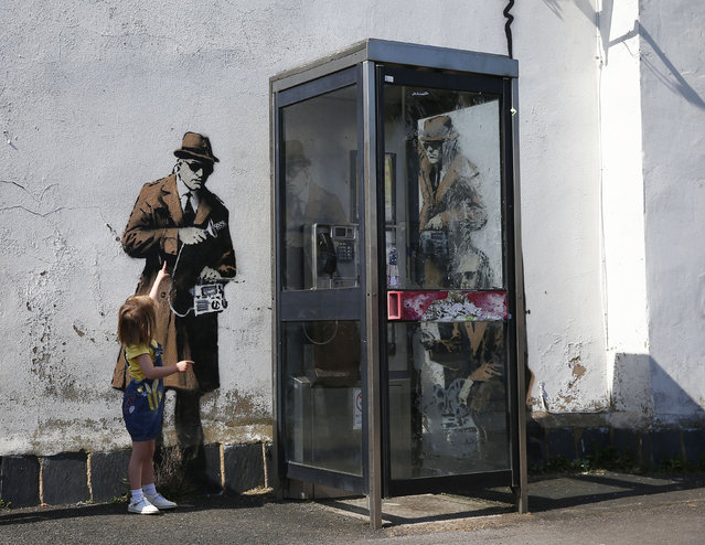 Polly Dreezer, age 3, points to graffiti art on a wall near the headquarters of Britain's eavesdropping agency, Government Communications Headquarters, known as GCHQ, in Cheltenham, western England April 16, 2014. British media have attributed the new work to acclaimed British street artist Banksy, as a spoof on recent government spying scandals exposed by former U.S. (Photo by Eddie Keogh/Reuters)