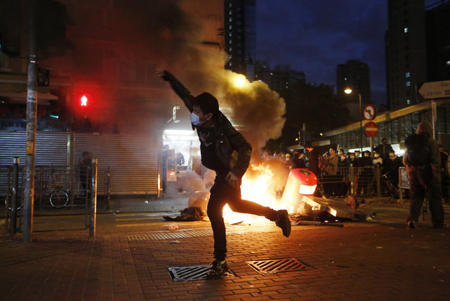 A rioter throws bricks at police and lit fires on streets in Mongkok district of Hong Kong, Tuesday, February 9, 2016. Rioters clashed with police overnight and into the early hours of Tuesday in a crowded area of Kowloon. The unrest started when local authorities tried to prevent street food sellers from operating on Monday night. Activists who are dissatisfied with Hong Kong's administration took part in the clashes, local media reports said. (Photo by Kin Cheung/AP Photo)