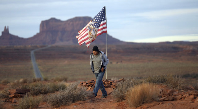 """In this Thursday, October 25, 2018, photo, Brandon Nez displays his flag at near his jewelry stand in Monument Valley, Utah, where tourists stand the highway to recreate a famous running scene from the movie """"Forest Gump"""". As Native American tribes around the country fight for increased access to the ballot box, Navajo voters in one Utah county could tip the balance of power in the first general election since a federal judge ordered overturned their voting districts as illegally drawn to minimize native voices. (Photo by Rick Bowmer/AP Photo)"""