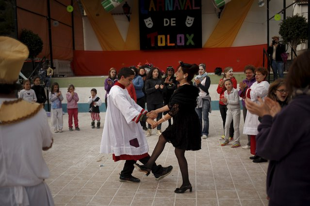 """A boy dressed up as an altar boy and a woman dressed up as a widow perform a traditional dance as they re-enact the traditional burial of the sardine during """"El Dia de los Polvos"""" (Powder Day) festival in Tolox, near Malaga, southern Spain, February 9, 2016. (Photo by Jon Nazca/Reuters)"""