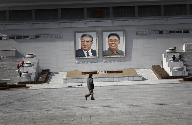 """A man walks past portraits of the late North Korean leaders Kim Il Sung and Kim Jong Il, at the Kim Il Sung Square on Sunday, February 14, 2016, in Pyongyang, North Korea. North Korea launched a rocket Feb. 7, carrying what it said was an Earth observation satellite into space. The U.N. Security Council condemned North Korea's launch of a long-range rocket that world leaders called a banned test of ballistic missile technology and another """"intolerable provocation"""". The U.N.'s most powerful body pledged to quickly adopt a new resolution with """"significant"""" new sanctions. (Photo by Wong Maye-E/AP Photo)"""