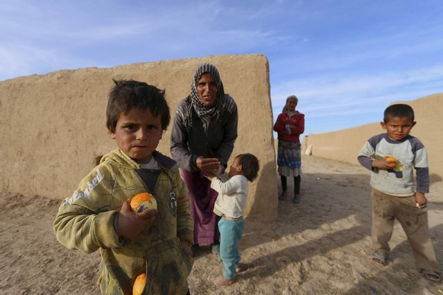 Children eat fruits in Ghazila village after fighters from the Democratic Forces of Syria took control of the town from Islamic State forces in the southern countryside of Hasaka, Syria February 17, 2016. (Photo by Rodi Said/Reuters)