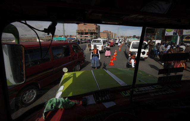 In this Dec. 3, 2013 photo, Aymara women traffic cops, seen through the windshield of a bus, direct traffic on the streets of El Alto, Bolivia. (Photo by Juan Karita/AP Photo)