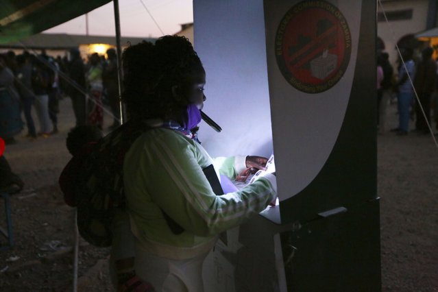 A woman uses her mobile phone to light the ballot box as she casts her vote at a polling station in Lusaka, Zambia, Thursday August 12, 2021. Zambias standing as one of Africa's most stable democracies is being tested as the country votes amid violence, alleged intimidation and fears of vote rigging. (Photo by Tsvangirayi Mukwazhi/AP Photo)