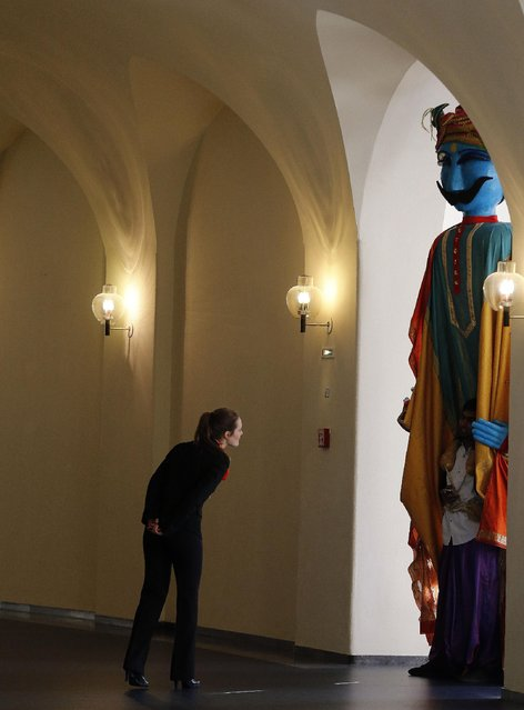 A woman looks at a giant puppet, a tradition in India which will be used at the opening of the industrial fair in Hanover, Germany, Sunday, April 12, 2015. India is this years partner country and participates in one of the worlds biggest industrial fair that lasts till April 17, 2015. (Photo by Frank Augstein/AP Photo)