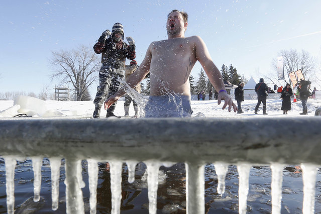 A man jumps into a hole cut in the ice on the Ottawa River during the annual Great Canadian Chill polar bear dip in Ottawa January 1, 2014. (Photo by Chris Wattie/Reuters)