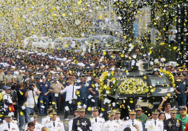"""Yellow confetti rain on the military component during the 30th anniversary celebration of the """"People Power Revolution"""" that toppled the 20-year-rule of the late strongman Ferdinand Marcos and helped install Corazon """"Cory"""" Aquino to the presidency, Thursday, February 25, 2016 at suburban Quezon city, northeast of Manila, Philippines. The four-day People Power saw hundreds of thousands of Filipinos trooping to EDSA Avenue fronting two military camps to lend support to mutinous soldiers who broke away from Marcos. (Photo by Bullit Marquez/AP Photo)"""
