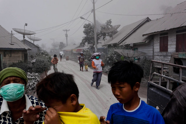 Villagers panic as they look for masks as their village is hit by ash from the eruption of Mount Sinabung in Payung village on January 8, 2014 in Karo District, North Sumatra, Indonesia. (Photo by Ulet Ifansasti/Getty Images)