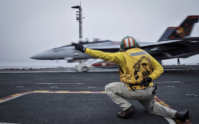 In this Wednesday, April 15, 2015 image released by the U.S. Navy, a shooter launches an F/A-18F Super Hornet, assigned to the Red Rippers of Strike Fighter Attack Squadron 11, off the flight deck aboard Nimitz-class aircraft carrier USS Theodore Roosevelt in the Fifth Fleet area of operations. he U.S. (Photo by Mass Communication Specialist Seaman Anna Van Nuys/U.S. Navy Media Content Services via AP Photo)