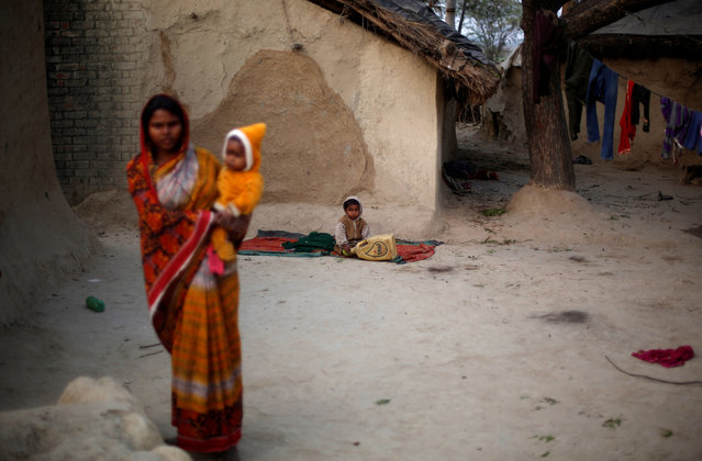 A wife of a snake charmer holds her baby as she stands outside her house in Jogi Dera (snake charmers settlement), in the village of Baghpur, in the central state of Uttar Pradesh, India January 16, 2017. (Photo by Adnan Abidi/Reuters)