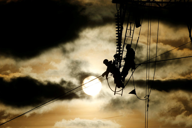 Technicians work on an electricity pylon as part of the maintenance of high-tension electricity power lines during sunset in Roye, France, February 11, 2019. (Photo by Pascal Rossignol/Reuters)