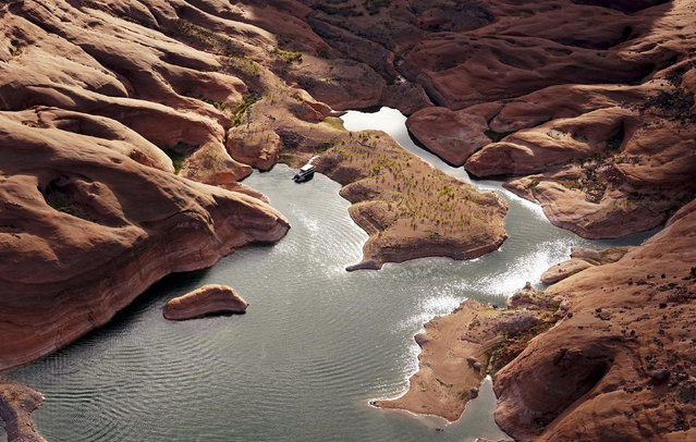 """""""Disappearing lake"""". Glen Canyon national recreation area, Arizona, US. A houseboat in shallow water in a canyon. The lake on the Colorado river provides water for Nevada, Arizona and California. In recent years, severe drought combined with withdrawals that many believe are not sustainable, has reduced water levels to about 42% of its capacity. (Photo by Rick Wilking/Reuters)"""