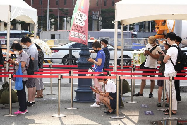 People wait to get coronavirus testing at a makeshift testing site in Seoul, Wednesday, July 28, 2021. South Korea reported a new daily high for coronavirus cases, a day after authorities enforced stringent restrictions in areas outside the capital region. (Photo by Ahn Young-joon/AP Photo)