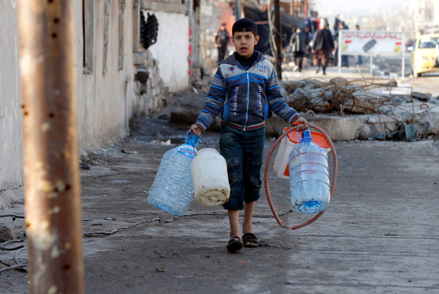 A boy collects water at al Zohour area in Mosul, Iraq, January 23, 2017. (Photo by Muhammad Hamed/Reuters)