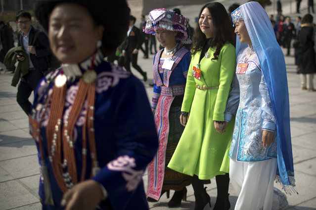 Delegates in ethnic minority dress leave after a meeting one day ahead of the opening session of China's National People's Congress (NPC) at the Great Hall of the People in Beijing, Monday, March 4, 2019. (Photo by Mark Schiefelbein/AP Photo)