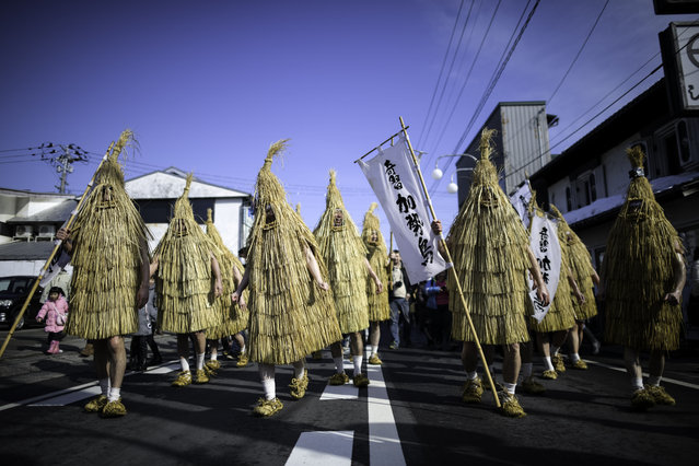 """Participants dressed in """"Kendai"""" or a bird shaped straw coats walks to the village to perform a dance during the """"Kasedori Festival"""" in Kaminoyama, Yamagata Prefecture, Japan, on February 11, 2019, to pray for good harvest, good fortune and fire prevention while local people wait in the streets with buckets and ladles to splash cold water onto the performers. (Photo by Richard Atrero de Guzman/NurPhoto via Getty Images)"""