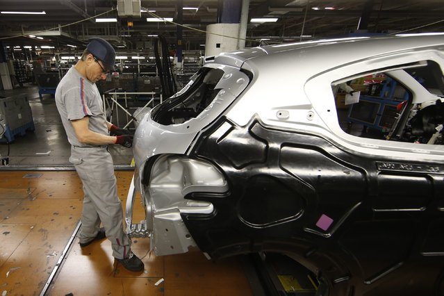 An employee works on the automobile assembly line of a Peugeot 208 car at the PSA Peugeot Citroen plant in Poissy, near Paris, France, April 29, 2015. (Photo by Benoit Tessier/Reuters)