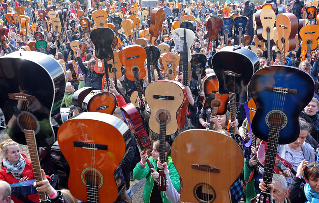 "Guitar enthusiasts raise their instruments after playing the Jimi Hendrix version of the song ""Hey Joe"" in an attempt to break the Guinness Guitar Record in Wroclaw, Poland, Friday, May 1, 2015. 5003 guitarists took part in the annual event, but not enough to break the number of musicians playing the tune. (Photo by Alik Keplicz/AP Photo)"