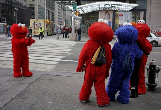 Characters dressed as Elmo and Cookie Monster who pose for tips take a photo by request from a tourist (2nd R, black pants) in Times Square in the Manhattan borough of New York City, January 29, 2016. (Photo by Rickey Rogers/Reuters)