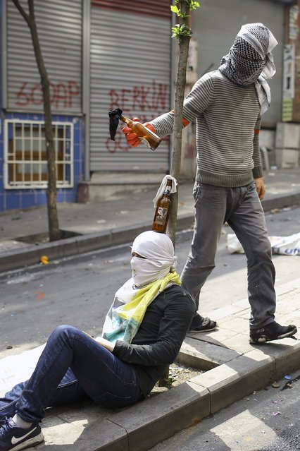 Two protesters play with Molotov cocktails during clashes with police in Okmeydani neighborhood in Istanbul, Turkey, May 1, 2015. (Photo by Huseyin Aldemir/Reuters)