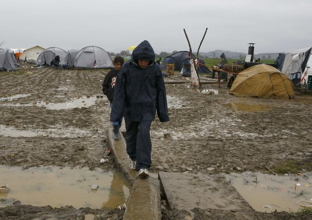 Boys walk over muddy puddles in a makeshift camp for migrants waiting to cross the Greek-Macedonian border, near the village of Idomeni, Greece March 15, 2016. (Photo by Ognen Teofilovski/Reuters)