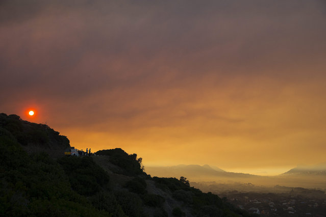The sun rises through thick smoke hanging over the Noordhoek Valley from a Fynbos vegetation fire on the World Heritage site Table Mountain National Park three days after it started in Muizenberg, Cape Town, South Africa, 03 March 2015. (Photo by Nic Bothma/EPA)