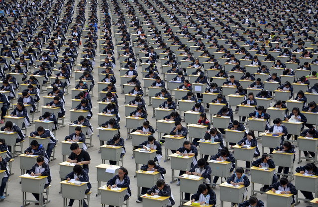 Students take an examination on an open-air playground at a high school in Yichuan, Shaanxi province April 11, 2015. More than 1,700 freshmen students took part in the exam, which was the first attempt by the school to take it in open-air. (Photo by Reuters/Stringer)