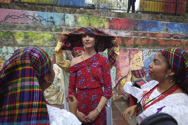 Jennifer Siebel Newsom, wife of California Gov. Gavin Newsom, receives help from dance students, to place on her head a traditional Panchimalco shawl worn by women in the last century, during a visit to Panchimalco, the home of indigenous Salvadorans, El Salvador, Monday, April 8, 2019. The governor and his wife later watched performances at a cultural center that aims to teach children traditional crafting, song and dance to help them build job skills in Panchimalco, a rural community surrounded by largely gang-controlled areas. (Photo by Salvador Melendez/AP Photo)