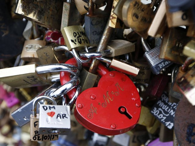 Every year, couples from all over the world flock to the bridge to attach padlocks of all shapes and sizes to its metal railing as a symbol of their love. (Photo by Charles Platiau/Reuters)