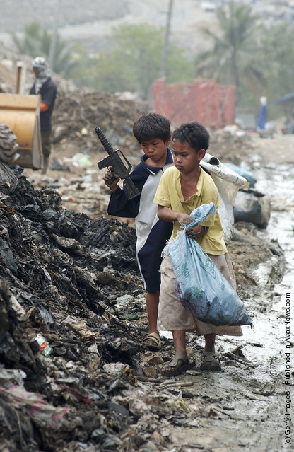Two young boys look for scrap metal in Metro Manila's largest landfill in one of the poorest neighborhoods of Payatas, Philippines
