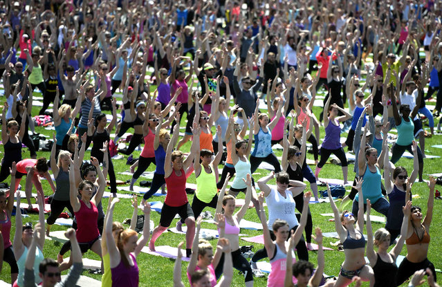 People take part in a yoga session on Parliament Hill in Ottawa on Wednesday, May 6, 2015. (Photo by Justin Tang/AP Photo/The Canadian Press)