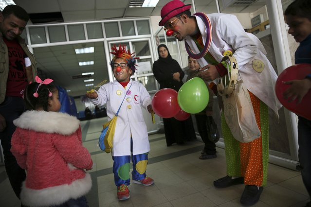 In this Thursday, March 17, 2016 photo, Palestinian clown doctors, 24-year-old Majed Kaloub, right, and 33-year-old Alaa Miqdad, center, entertain children at Al-Rantisi children's hospital in Gaza City. (Photo by Adel Hana/AP Photo)
