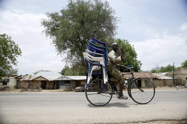 A man rides a bicycle along a road in Michika town after the Nigerian military recaptured it from Boko Haram, in Adamawa state May 10, 2015. (Photo by Akintunde Akinleye/Reuters)