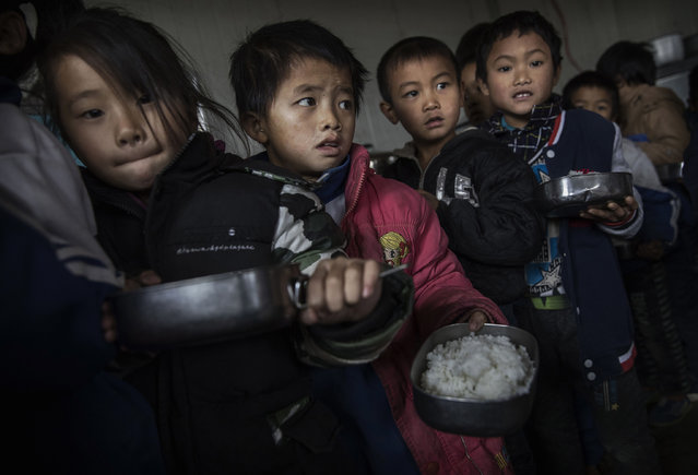 """""""Left behind"""" childern is served lunch at a local school on December 16, 2016 in Anshun, China. (Photo by Kevin Frayer/Getty Images)"""