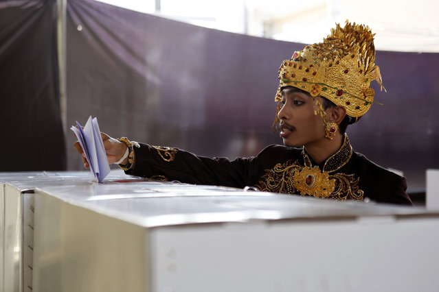 A Balinese groom casts his ballot at a polling station during election in Bali, Indonesia Wednesday, April 17, 2019. Tens of millions of Indonesians were voting in presidential and legislative elections Wednesday after a campaign that pitted the moderate incumbent against an ultranationalist former general whose fear-based rhetoric warned the country would fall apart without his strongman leadership. (Photo by Firdia Lisnawati/AP Photo)