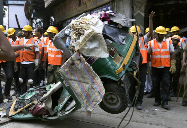 A damaged three-wheeled vehicle is taken out from the rubble of a collapsed overpass in Kolkata, India, Friday, April 1, 2016. (Photo by Bikas Das/AP Photo)