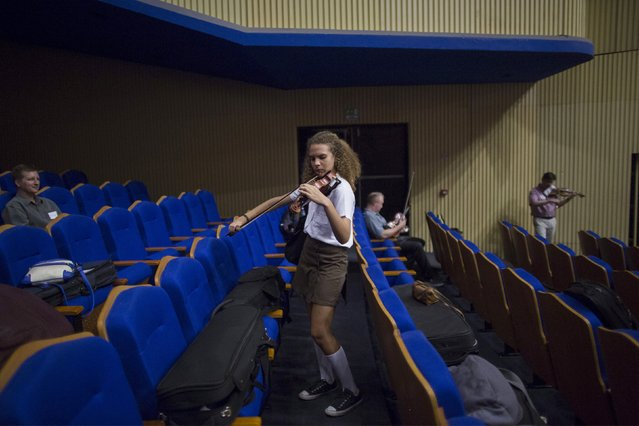 Music student Tania Haase, 16, practices violin during a break at the rehearsal with the Minnesota Orchestra in Havana, May 15, 2015. (Photo by Alexandre Meneghini/Reuters)
