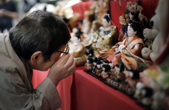 A visitor looks at sacrificed dolls during the Festival of Repayment of Kindness at Dairoku-tensakaki Shrine in Tokyo, Saturday, May 16, 2015. Traditionally, it is believed that the dolls can give good health and happiness to children by absorbing sickness and ill fate. The dolls are then sacrificed during the festival after they have protected their young owners. (Photo by Eugene Hoshiko/AP Photo)