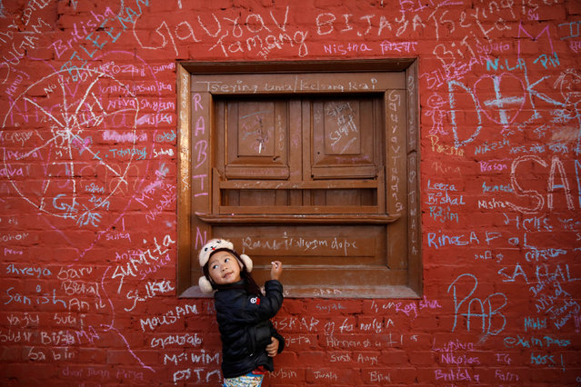 A girl looks towards her father as she writes on the wall of a Saraswati temple during the Shreepanchami festival dedicated to goddess of education Saraswati in belief that the goddess will help devotees excel in education, in Kathmandu, Nepal February 10, 2019. (Photo by Navesh Chitrakar/Reuters)