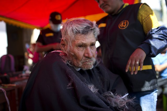 Eustaquio Rodriguez, 86, sits for a free haircut in a tent converted in a makeshift barbershop in Surcubamba, Peru, Thursday, May 21, 2015. (Photo by Rodrigo Abd/AP Photo)