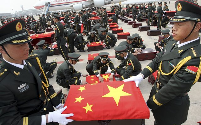 Soldiers of the Chinese People's Liberation Army (PLA) hold caskets containing the remains of soldiers of the Chinese People's Volunteers (CPV) in Shenyang, Liaoning province, March 28, 2014. The remains of 437 Chinese soldiers killed during the 1950-53 Korean War returned to China from a temporary columbarium in South Korea. (Photo by Reuters/China Daily)