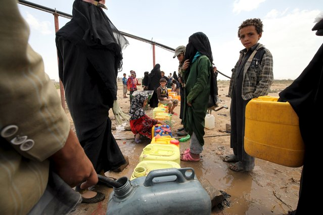 People fill jerrycans with water from a public tap amidst an acute water shortage in Sanaa May 13, 2015. (Photo by Mohamed al-Sayaghi/Reuters)