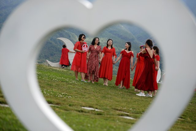 Women posing for pictures are seen through a heart-shaped prop near Erhai Lake in Dali Bai Autonomous Prefecture, Yunnan province, China on June 15, 2019. (Photo by Tingshu Wang/Reuters)