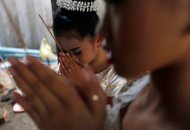 Dancers pray before they perform as land activists gather to commemorate the upcoming Women's Day in Phnom Penh, Cambodia, March 7, 2017. (Photo by Samrang Pring/Reuters)